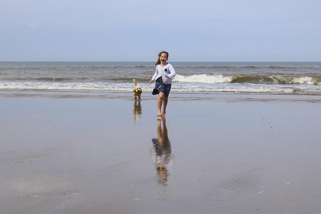 dívka se psem na pláži