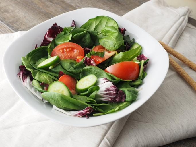 Talířek se zeleninou, na šedém ubrusu, obsahuje rajče, okurek a salát